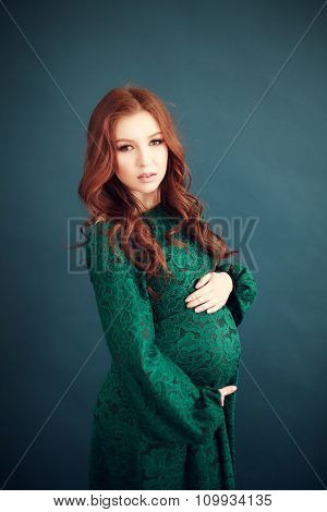 Pregnant woman in long lace green dress
