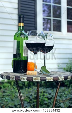 Bottle Of Wine And Glasses On A Garden Table