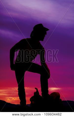 Silhouette Of A Cowboy Stand With Foot On Saddle Hand On Knee