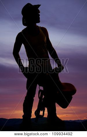 Silhouette Of A Young Man Holding A Saddle
