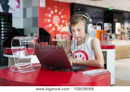 BEIJING - CIRCA JUNE, 2015: Boy with headphones using a laptop in the Lenovo store is on a Qianmen street in the center of  Beijing. Lenovo Group Limited - world-famous Chinese computer company.