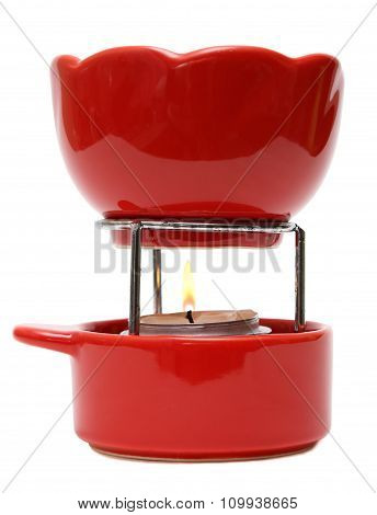 Red ceramic fondue set appliance isolated on white background.