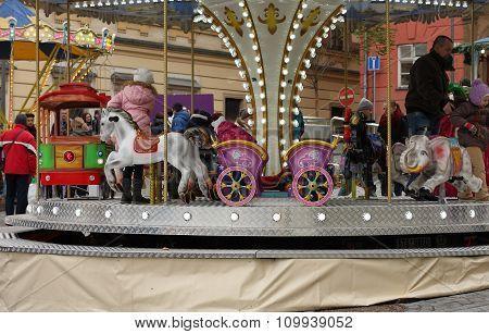 Children On Roundabout On Christmas Market