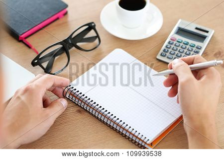 Male Hand Holding Silver Pen Ready To Make Note In Opened Notebook.