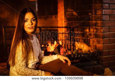 Woman Relaxing At Fireplace. Winter Home.
