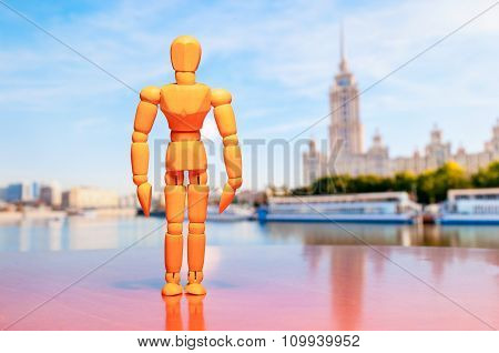 Wooden dummy, mannequin or man figurine stand against the backdrop of Moscow, Russia