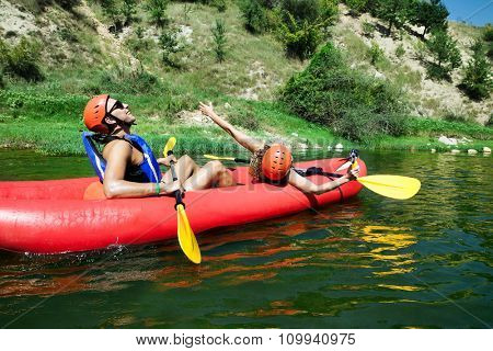 A male and female in a red inflatable canoe celebrating reaching calm waters of a river.