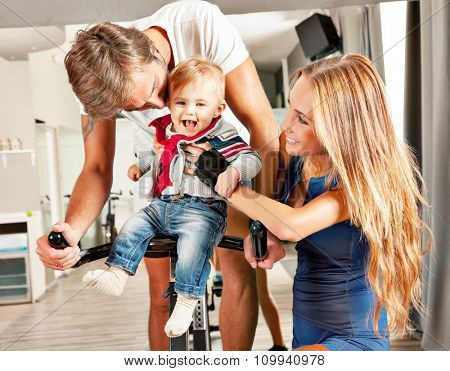 Young beautiful mother and father having fun embracing their cute  little boy with affection in a cycling gym.