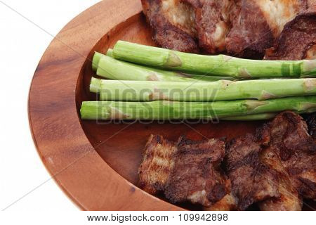 dinner of hot grilled beef meat ribs served with asparagus on wooden plate isolated on white background