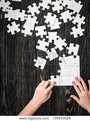 hands starting to collect puzzle pieces on dark wooden table