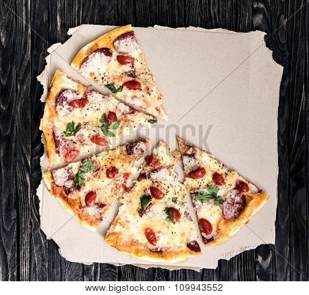half portions of pizza on parchment isolated on dark wooden background top view