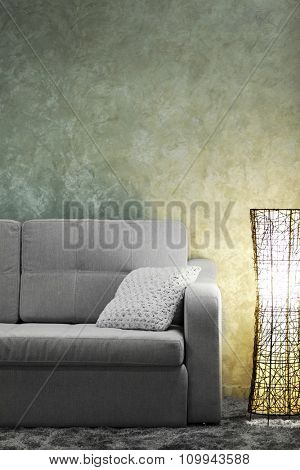 Comfortable sofa and modern lamp on grey wall background