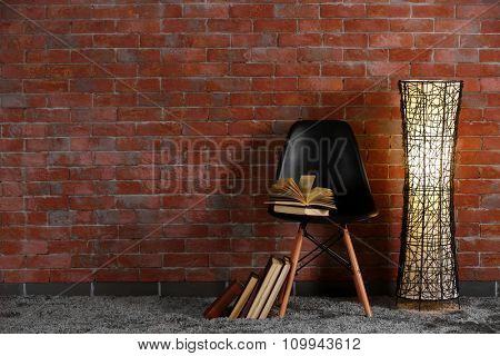 Black modern chair with lamp and books on brick wall background