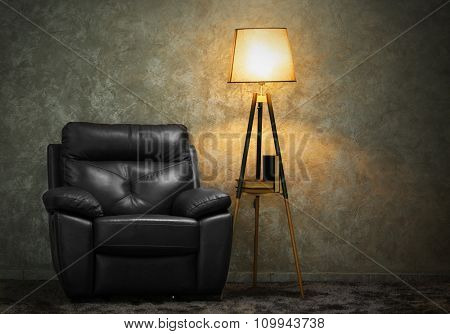 Black leather chair and lamp on grey wall background