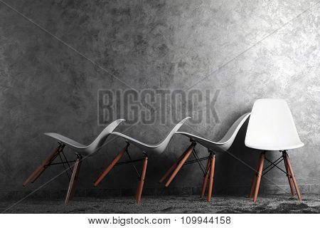 Stylish conception with white chairs on grey background