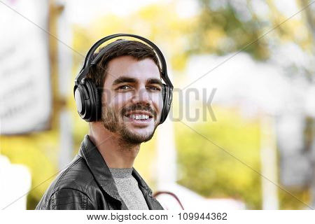 Young man listening to music and walking along the street