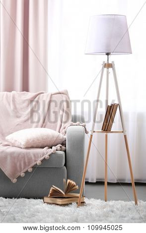 Comfortable sofa with lamp and book against window in the room