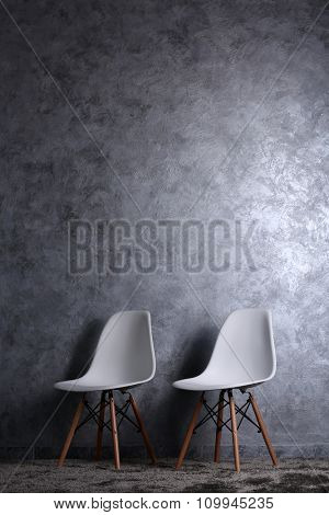 Stylish conception with two white chairs on grey background