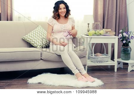 Cute happy pregnant woman on sofa in the room
