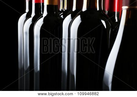 Wine bottles on dark background, close up