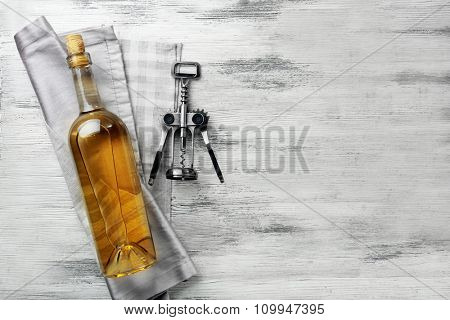 Wine with corkscrew on a light wooden background