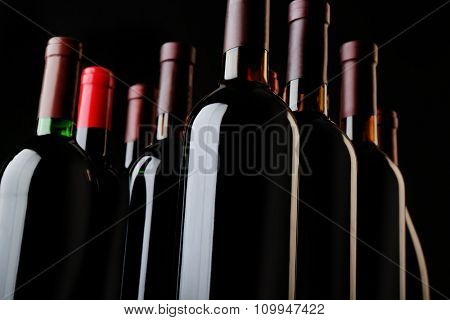 Wine bottles on black background, close up