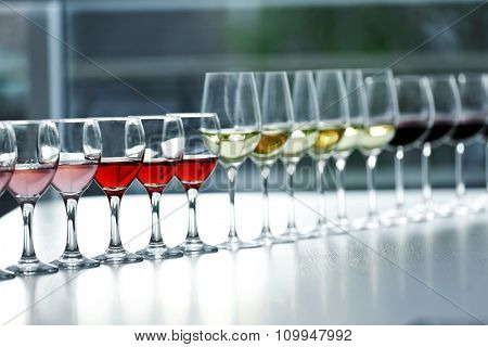 Wineglasses with white, red and pink wine on wooden table on bright background