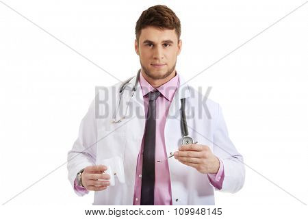 Male dentist holding a mirror and tooth model.