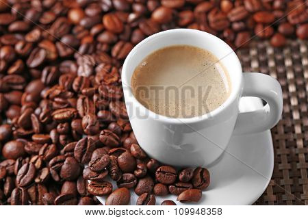 Cup of coffee and coffee grains on dark background