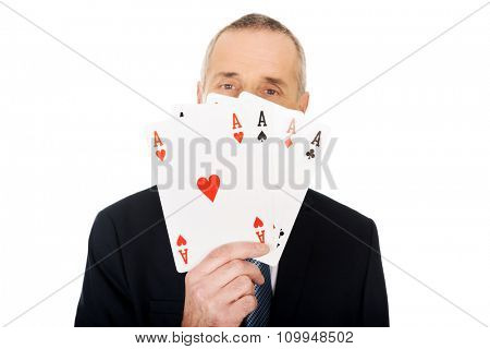 Smart mature man with four aces.