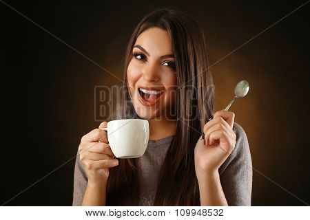 Happy beautiful woman with cup of coffee and spoon on dark background