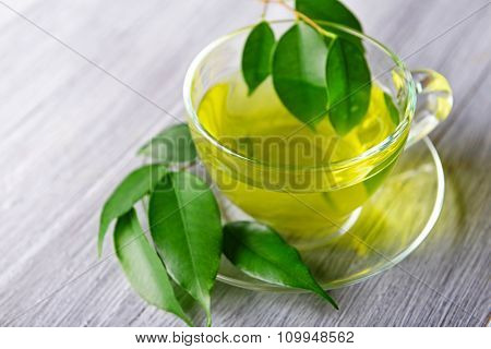 Glass cup of tea with green leaves on grey wooden background