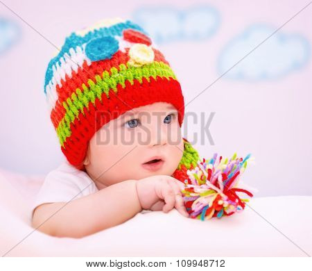 Portrait of cute little baby wearing colorful warm hat relaxing in cozy children's room, healthy lifestyle, happy carefree childhood