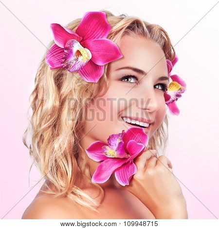 Closeup portrait of cute happy female with orchid flower over pink background, enjoying aromatherapy and natural beauty treatment