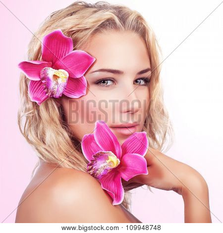 Portrait of beautiful blond woman with pink orchid flower in hair and in hand over clear background, enjoying day spa