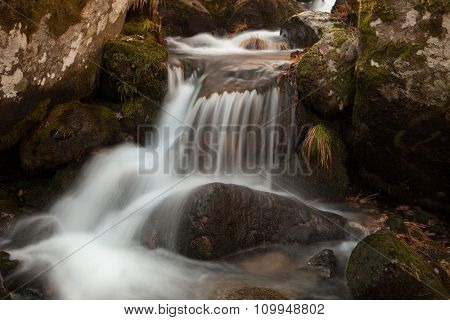 Beautiful waterfall falling on a stones with moss