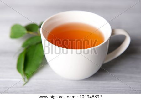 Ceramic cup of tea with green leaves on light wooden background
