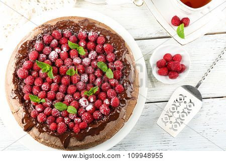 Cake with Chocolate Glaze and raspberries and cup of tea on color wooden background