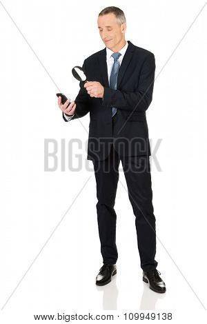Businessman reading a message with magnifying glass