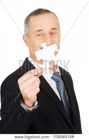 Smart mature businessman holding a puzzle
