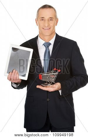 Mature businessman holding shopping cart and tablet.