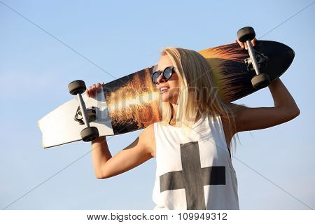 Young woman with skating board on blue sky background