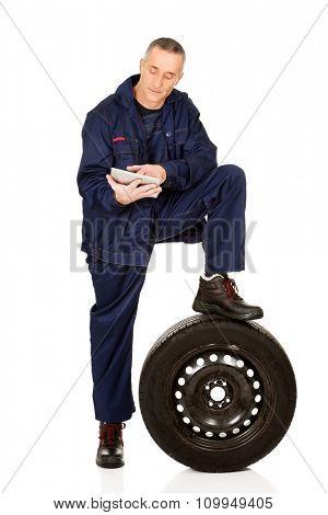 Mature car mechanic using a tablet.