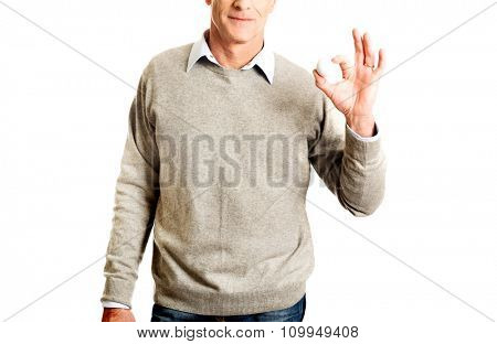 Active mature man holding golf ball.