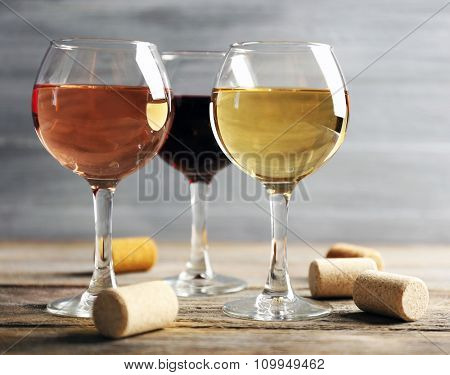 Composition of wine glasses and corks on wooden table against grey background