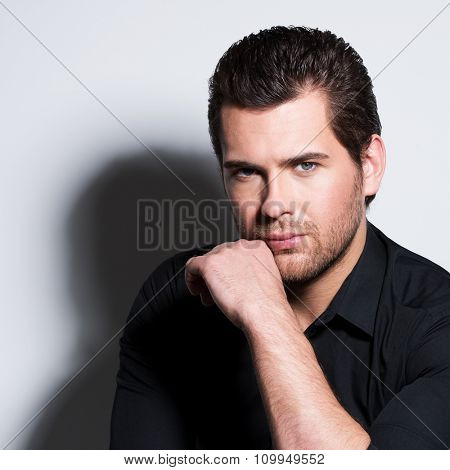 Fashion portrait of handsome man in black shirt with hand near face poses in the studio.
