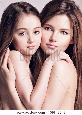 Beautiful naked mother and small daughter 8 years with long brown hair embrace each other at studio