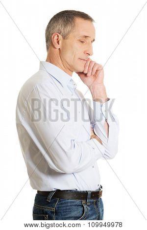 Side view pensive man touching chin.