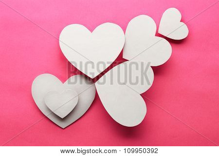 White paper hearts on pink background