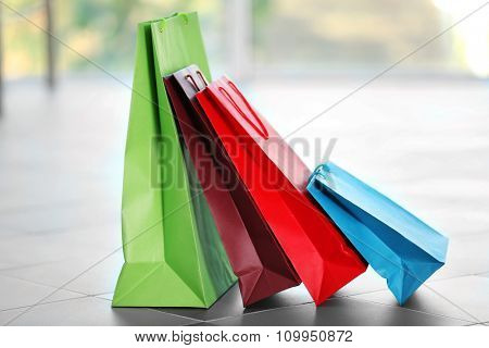 Colourful paper shopping bags on defocused background